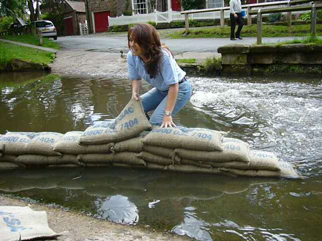 Lady up to her angles in flood building a sandbag wall